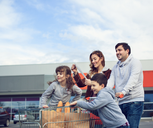 Cheerful family going back from supermarket. Pushing shopping cart and carrying shopping bags. Mother looking at shop bill.